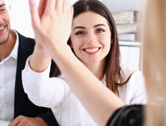 Two girls going high-five in the office