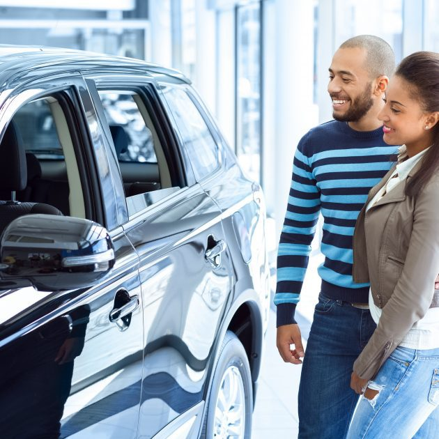 Young Couple looks happy with the purchase of new car