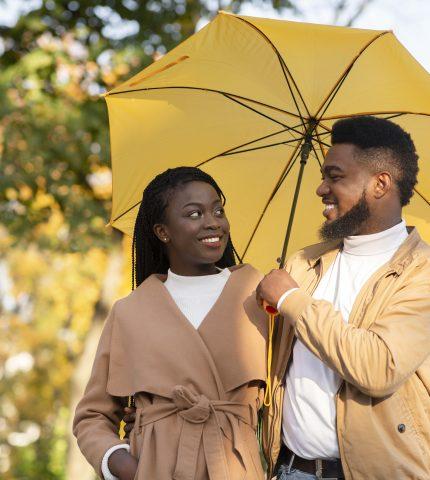 Happy afro couple walking under umbrella in autumn park