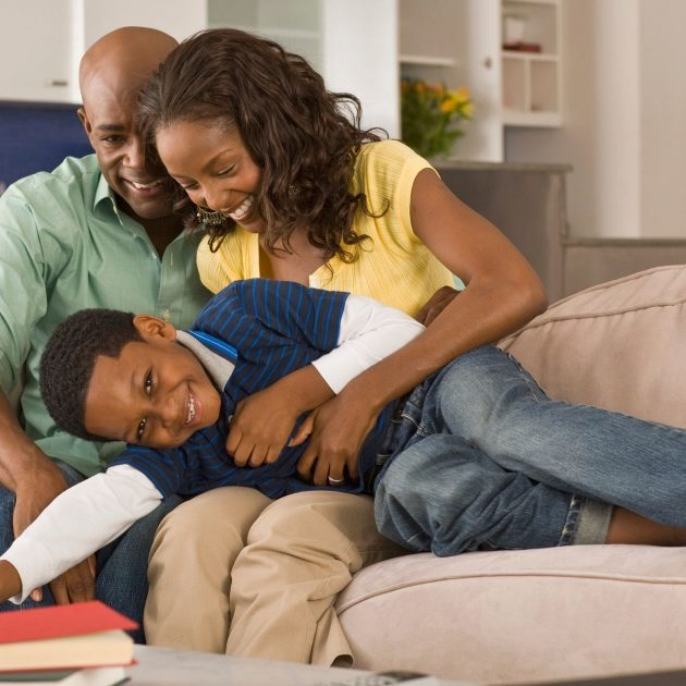 Couple playing with it's kid on the sofa
