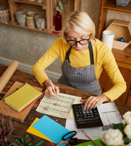 Mature Woman doing an Accounting for her Business Insurance Policy