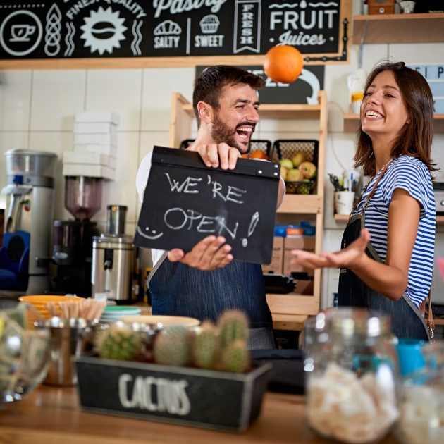 Business owner holding Open Sign and Girl looks happy