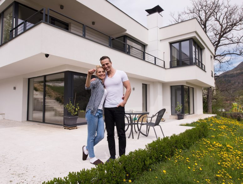 Portrait of a happy young couple hugging in front of their new luxury home