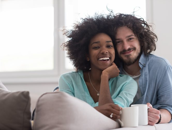 multiethnic couple sitting on sofa at home drinking coffee and talking