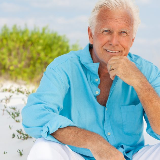 Senior citizen looks happy and seated on the sand near beach