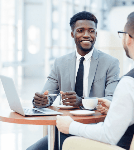 Two Men discuss about Choice Insurance Referral Program at office