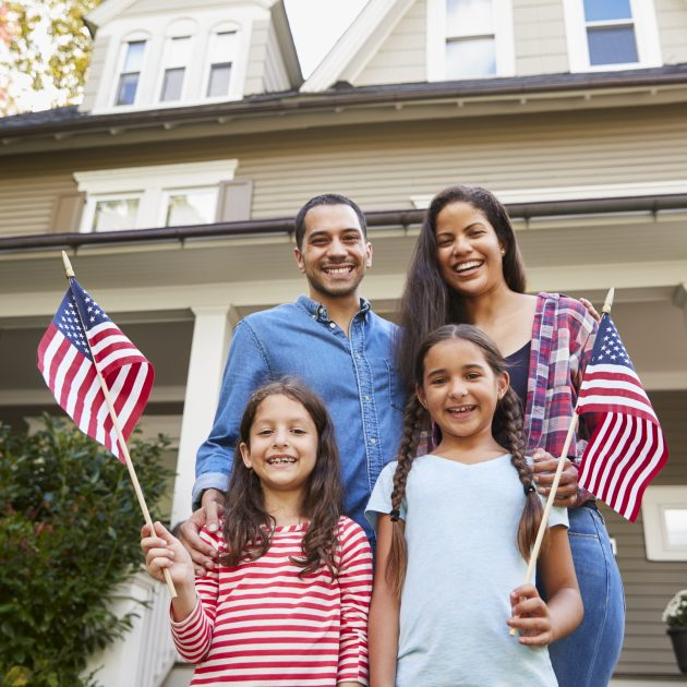 Family hold the flag of United States and looks happy outside their home